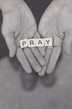 word pray in scrabbles pieces in a woman's hands
