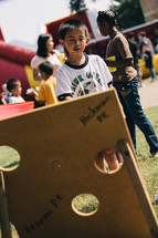 a child playing bean bag toss