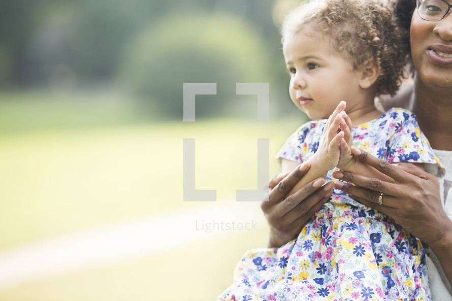 mother and toddler daughter outdoors clapping hands