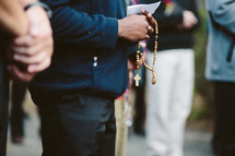 Young catholic man praying the rosary in a group outside