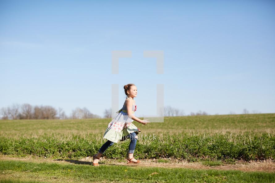 a girl running in a field of grass