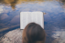 woman sitting on a rock reading a Bible by a river