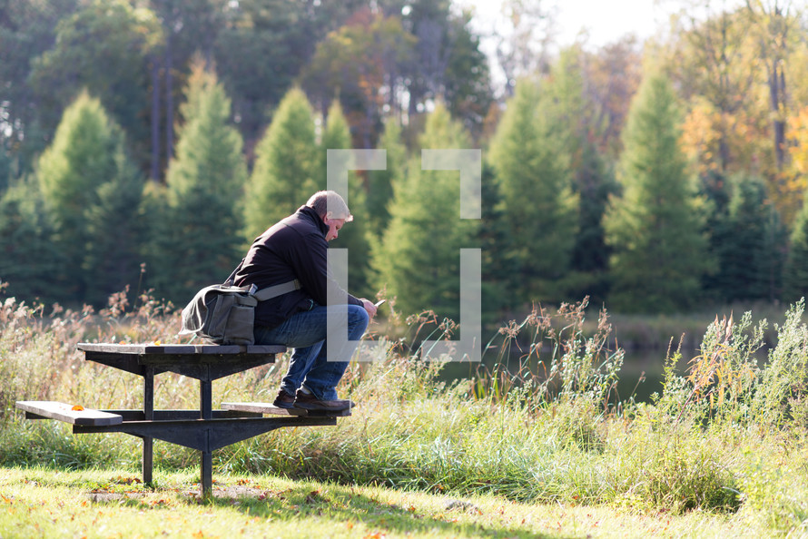 man sitting on a picnic table by a river