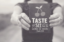 woman holding a sign that reads, Taste and see that the lord is good, Psalm 34:8