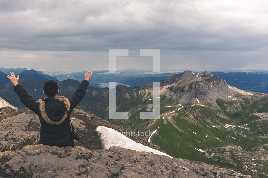 a man with a camera and raised hands sitting on a mountaintop