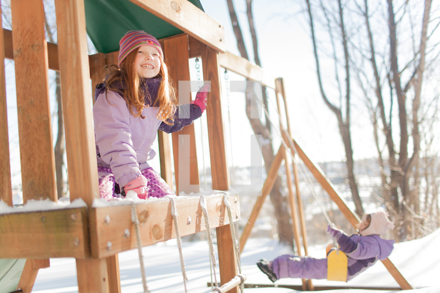 children on a backyard swing set in winter