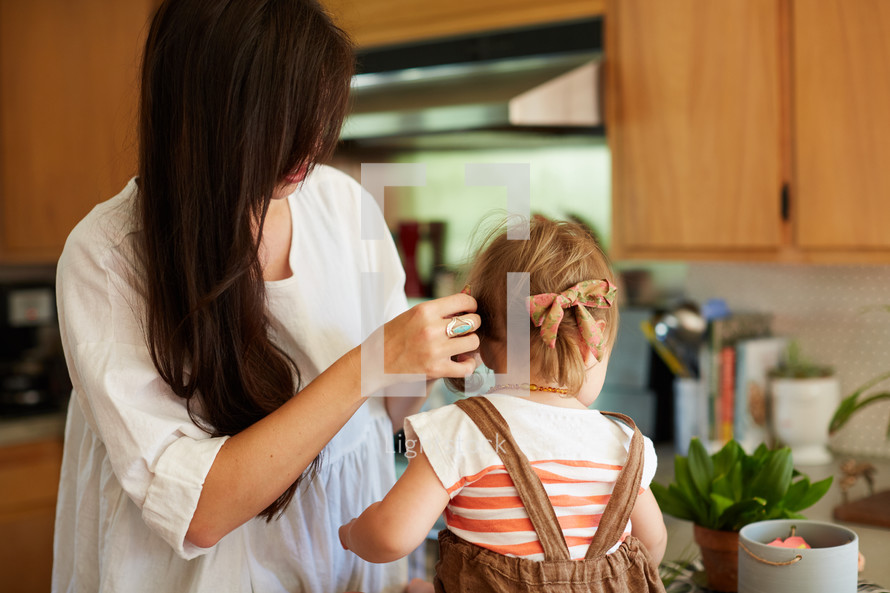 a mother fixing her daughters her on a countertop in a kitchen