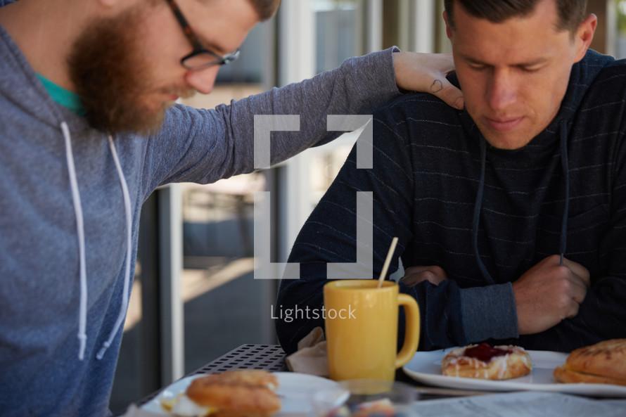 men saying grace before breakfast