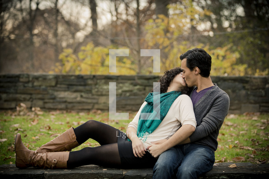 Woman leaning back on on man kissing as they sit in the park.