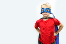 Little  boy dressed as superhero with red shirt and blue mask and cape on white background.