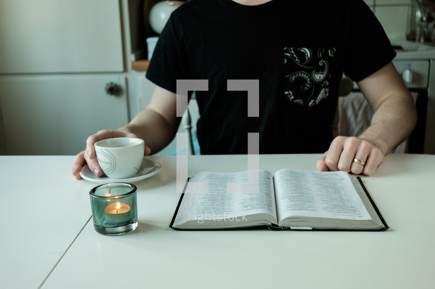 a man with a tea cup and open Bible