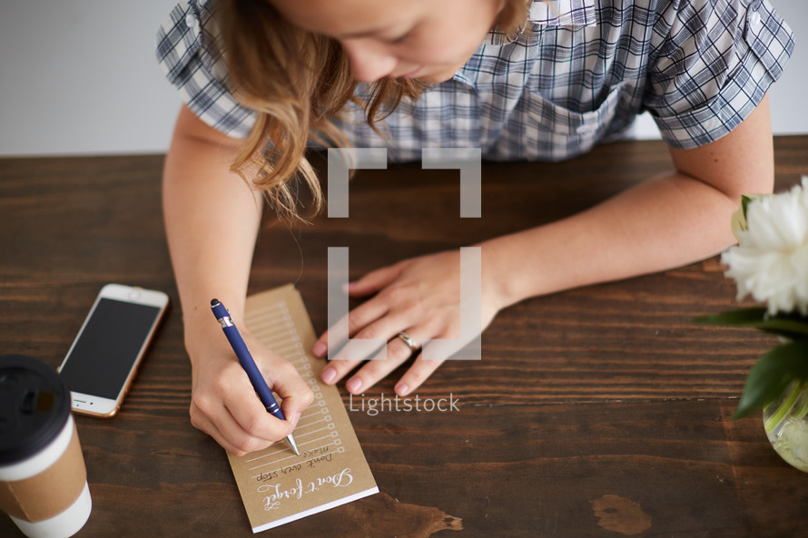 a woman taking notes on a notepad