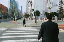 a man crossing a crosswalk in a city