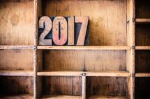 "Wooden letters spelling ""2017"" on a wooden bookshelf."
