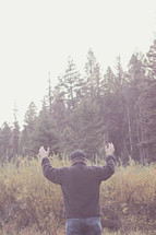 man standing in a field with raised hands