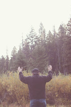 man standing outdoors with raised hands