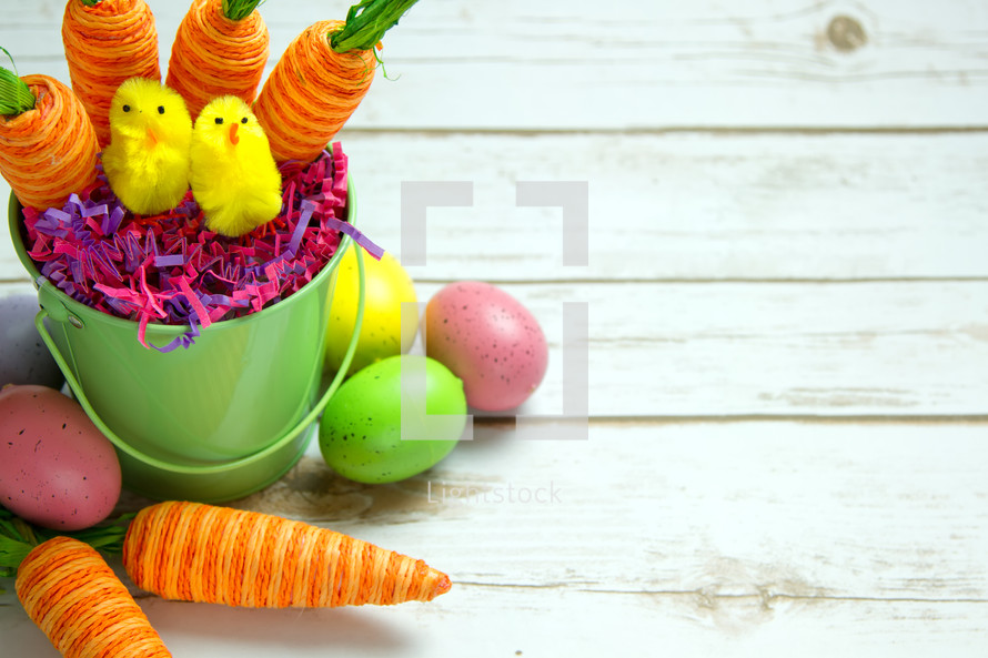 Easter eggs and carrot decorations in an Easter basket on white wood boards