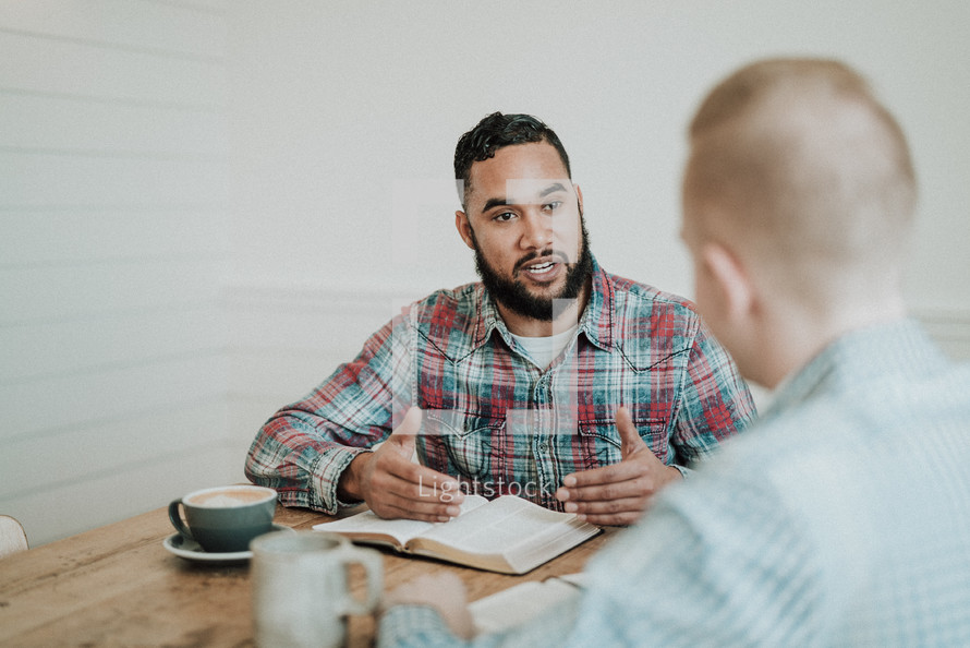 two men sitting at a table reading Bibles and discussing scripture