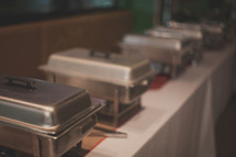 Stainless steel warming pans lined up on a table.