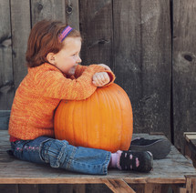 a child sitting with a pumpkin