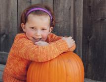 a little girl sitting with a pumpkin