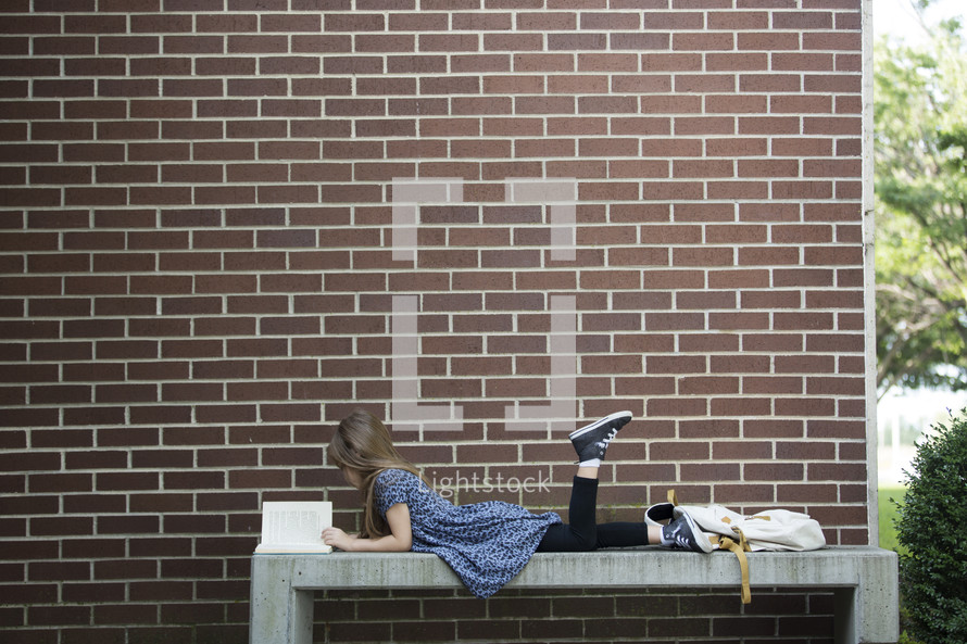 a child sitting on a bench reading a book while waiting for school to start