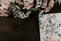 happy mother's day card and flowers on a wood background