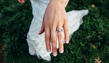 an engagement ring and wedding band on a bride