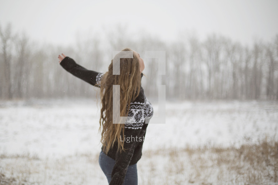 a young woman standing in the snow
