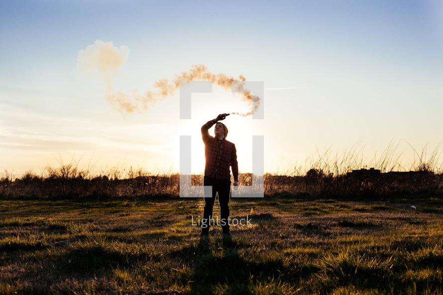 man waving a smoke flare