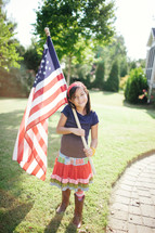 girl child holding an American flag in front of her house