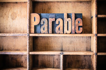 "Wooden letters spelling ""parable"" on a wooden bookshelf."