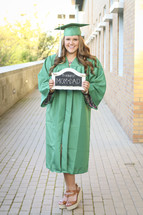 graduate holding a thanks mom and dad sign