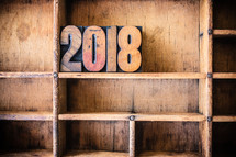 "Wooden letters spelling ""2018"" on a wooden bookshelf."