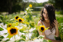 A young woman in a field of sunflowers.