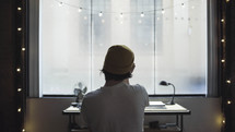man looking out a window in an apartment