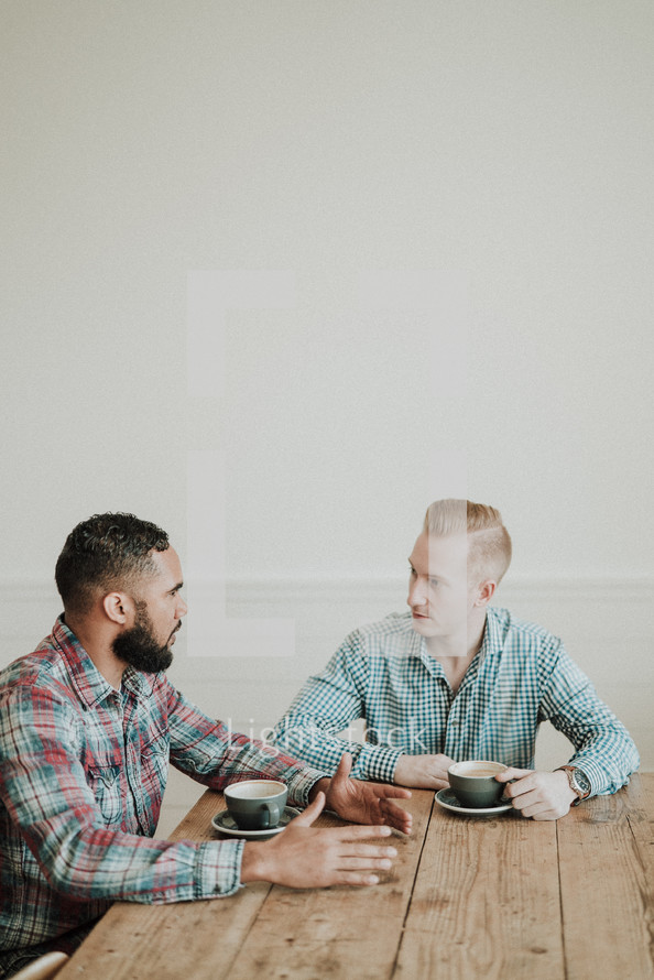 two men talking over coffee
