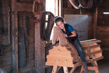 a girl sitting on a wooden horse in a barn
