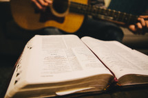 A man playing a guitar while reading a Bible.