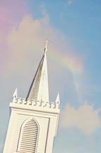 white church steeple and rainbow