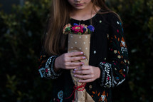 a girl holding a bouquet of flowers