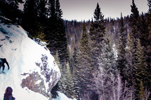 snow on rocks on a mountainside and trees