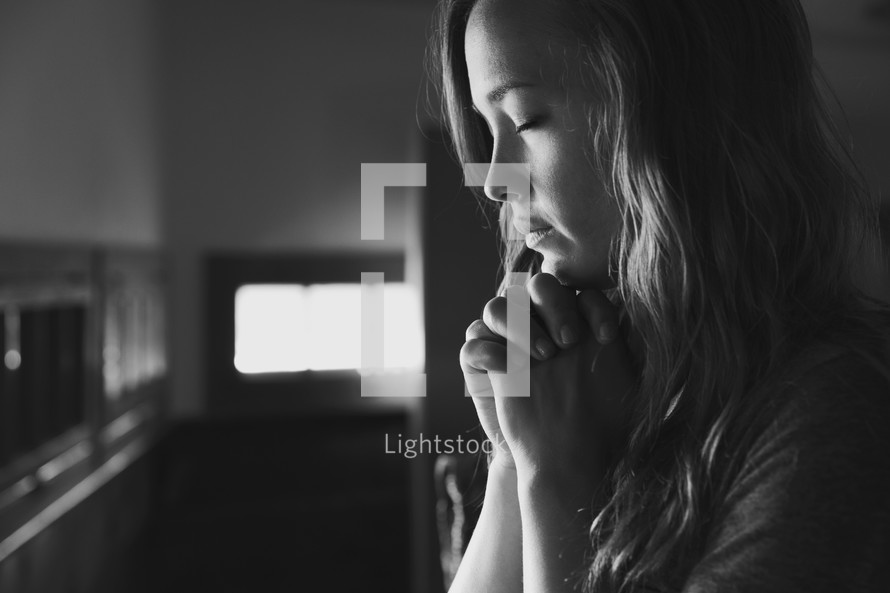 a young woman in prayer at a church.