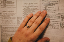 A woman's hand on the pages of a Bible.
