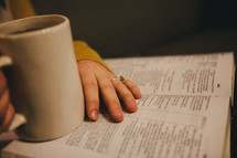 A woman drinking coffee while reading a Bible.