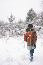 woman backpacking through snow