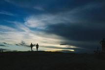 silhouettes of people standing on a mountain top