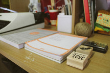 vintage typewriter, notepads, and rubber stamps on a desk