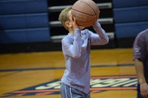 a child shooting a basketball
