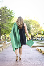 a graduate walking carrying her cap and gown